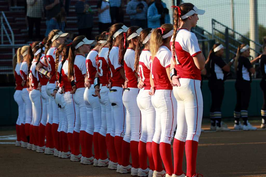 Varsity+team+stands+at+attention+for+the+singing+of+the+national+anthem.