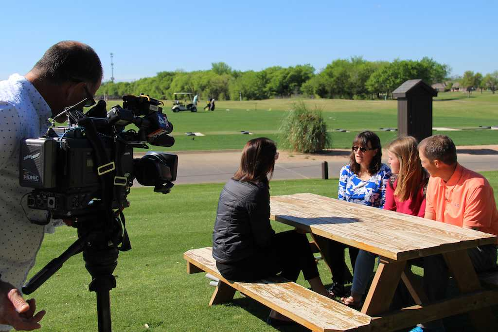 Junior Savanna Roulette sits with her mother Trish and golf coach Kevin Johnson as she is interviewed by FOX 4 regarding her charity golf tournament.