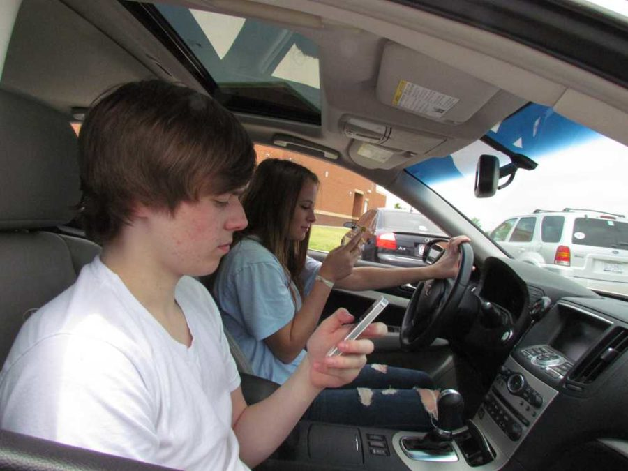 Sophomores+Michael+Jones+and+Clare+Keil+are+both+on+their+phones+will+driving+through+the+parking+lot.