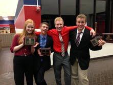Debate team members Bryce Broomham, Nate Wutzke, Avery Flessner, and Emma Holmes present their trophies.