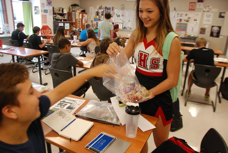 The cheerleaders are selling lollipops around campus to raise money for future trips.