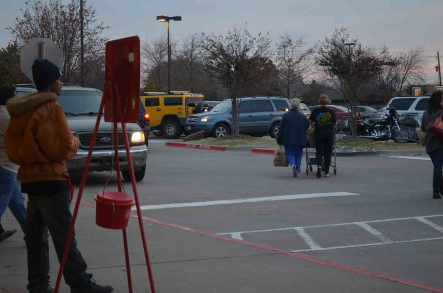 Volunteers stand outside in the cold temperatures ringing a handheld bell encouraging people to donate to the Red Kettle for Salvation Army.