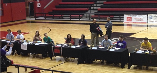 Sitting at tables in the LHS gym, nine seniors sign athletic scholarship offers on Signing Day, Feb. 5, 2014.