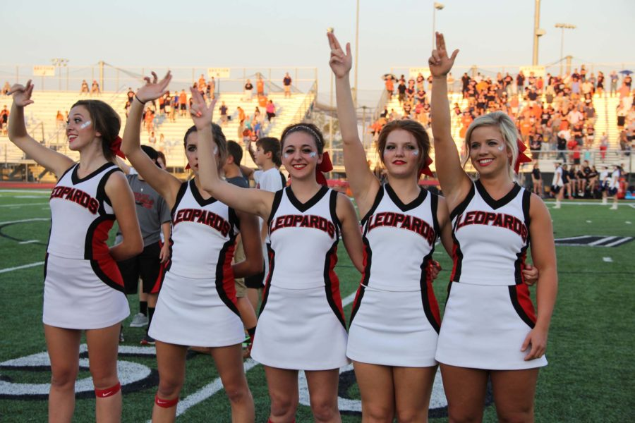Varisty cheerleaders show the 'double L' to show support for the team.