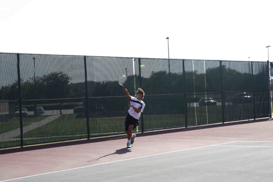 Junior, Grady Wells, serves the ball while hoping to ace his opponent.