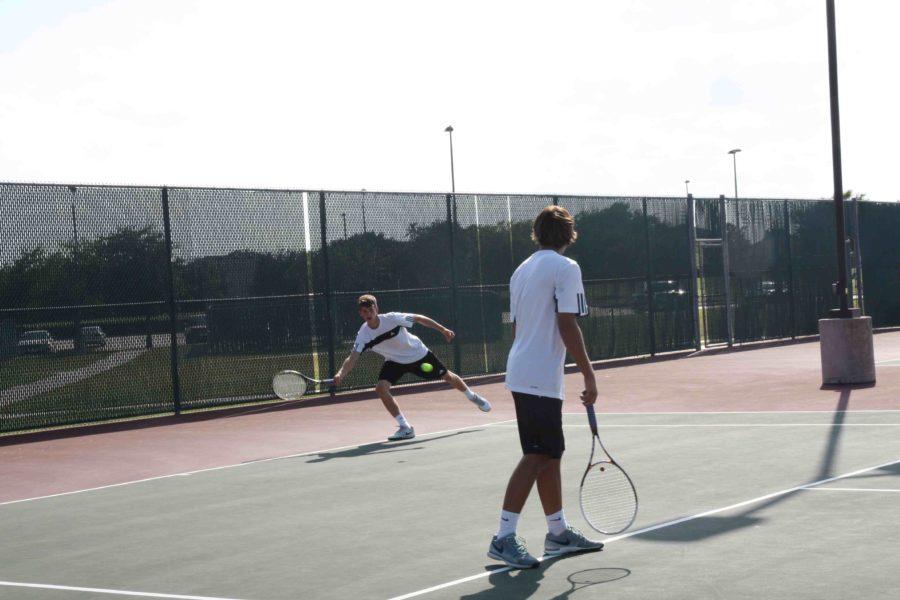 Junior, Cole Bennett, returns the his opponents serve.