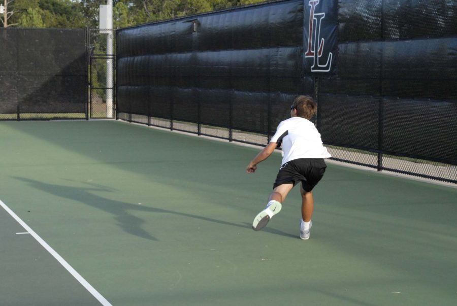 Junior+tennis+player+Grady+Wells+goes+after+the+ball+to+continue+the+volley.+