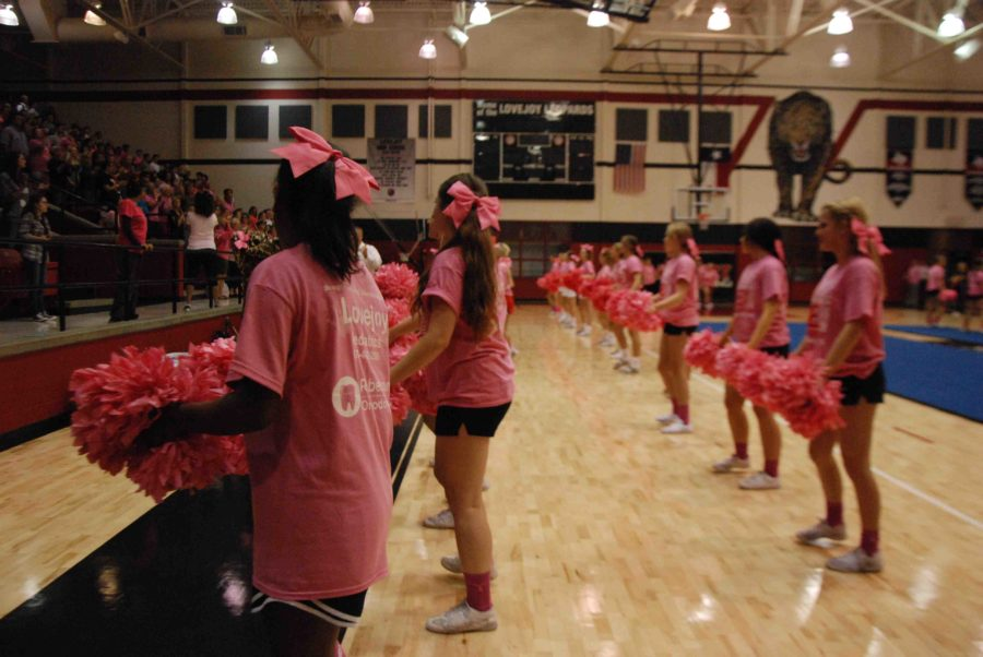 Cheerleaders wear completely pink attire to the Pink Out pep rally on Oct. 17, 2014, including pink shirts, bows, socks, and pom-poms.