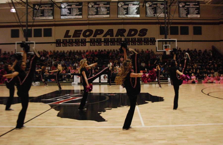 Majestics Emma Lagare, Lexi Seay, Katelyn Kaya, and Jennifer Kaya perform a high-kick during their performance in the Pink Out pep rally on Oct. 17, 2014.