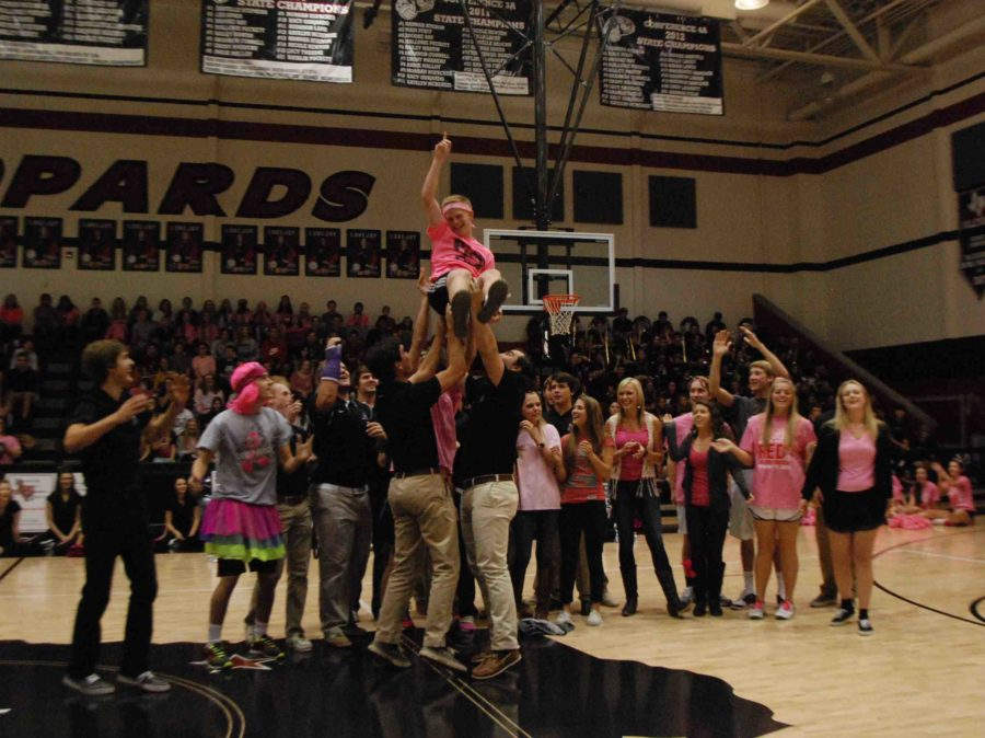 Seniors Mac Metzler and Tommy OConnor lift Matt Smith in a spirit competition in the Pink Out pep rally on Oct. 17, 2014.