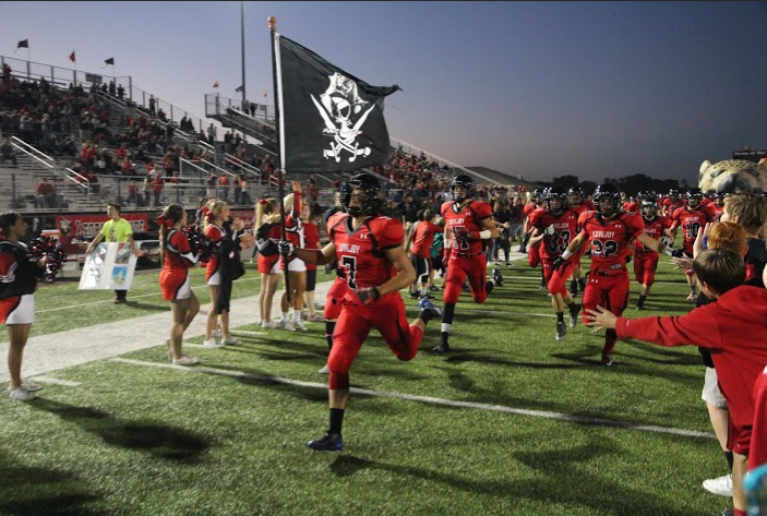 Lovejoy+Defensive+Back+Kyle+Canella+%287%29%2C+a+senior%2C+leads+the+team+down+the+spirit+line+carrying+a+Jolly+Roger+flag%2C+a+symbol+for+the+team%27s+defensive+end.