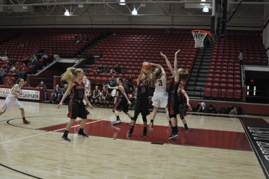 Senior Paige goes up for a shot even though she is heavily guarded by the opposing team.