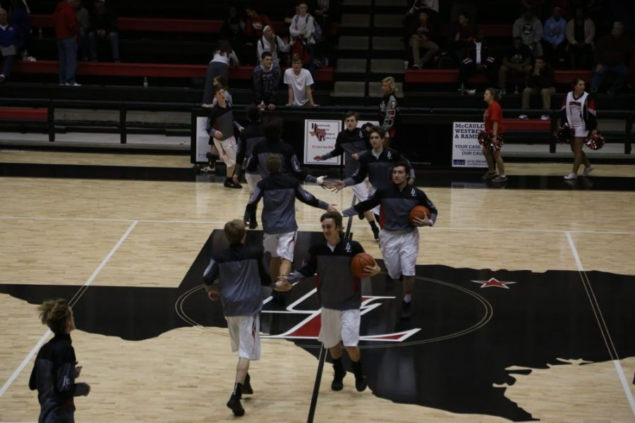 The Leopard Basketball team members high-five each other as they come onto the court to warm up.