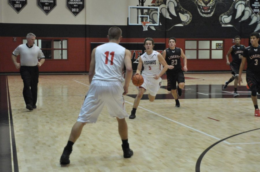 Senior Adam McDaniel brings the ball down court, beating two of the opposing teams players