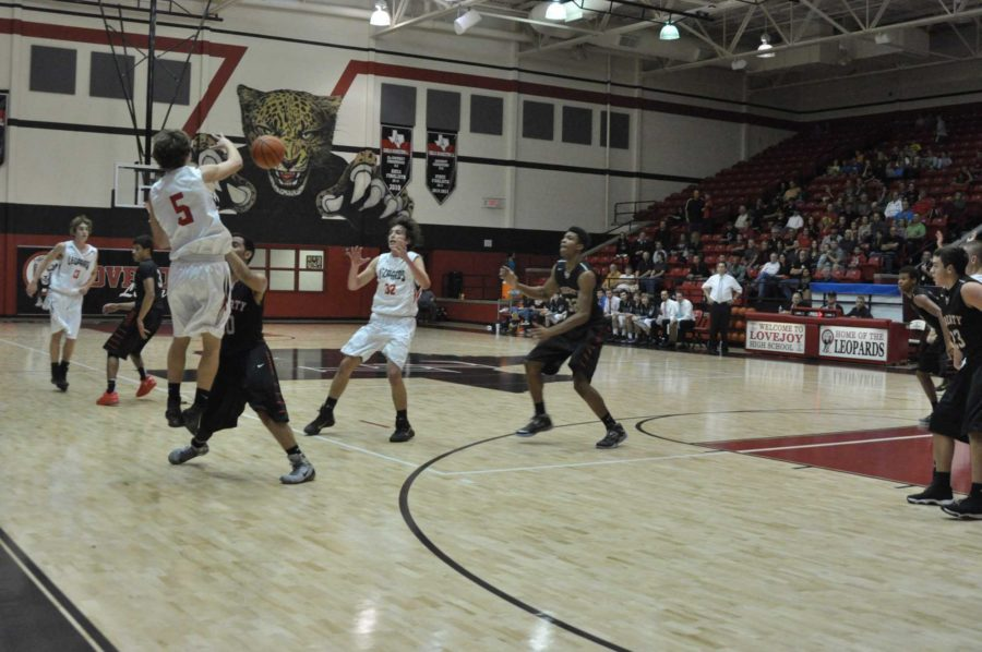 Senior Adam McDaniel jumps over his defender to pass to