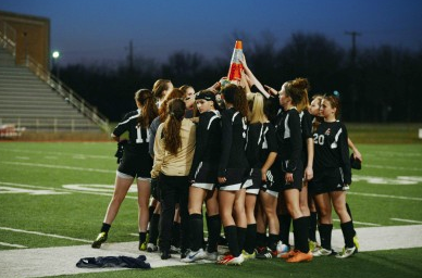 Following tradition, Lovejoy girls soccer team huddles around their playoff cone.