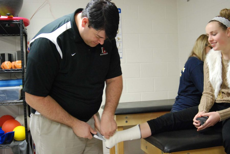Athletic trainer and Medical Terminology teacher Johnathan Stinson tapes an athlete's ankle to prevent injury.