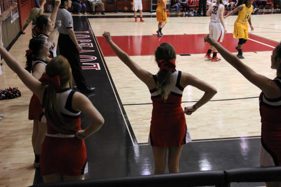 Several varsity cheerleaders cheer for the Lady Leopards game against Denison with smiling faces. The team splits its members so that both boys and girls basketball players receive their support.