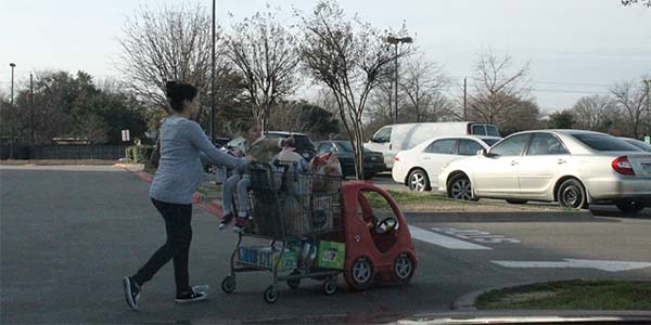 A woman exiting Kroger is carrying her items in plastic bags. If this were in Dallas, she would have to pay a fee to use such bags.