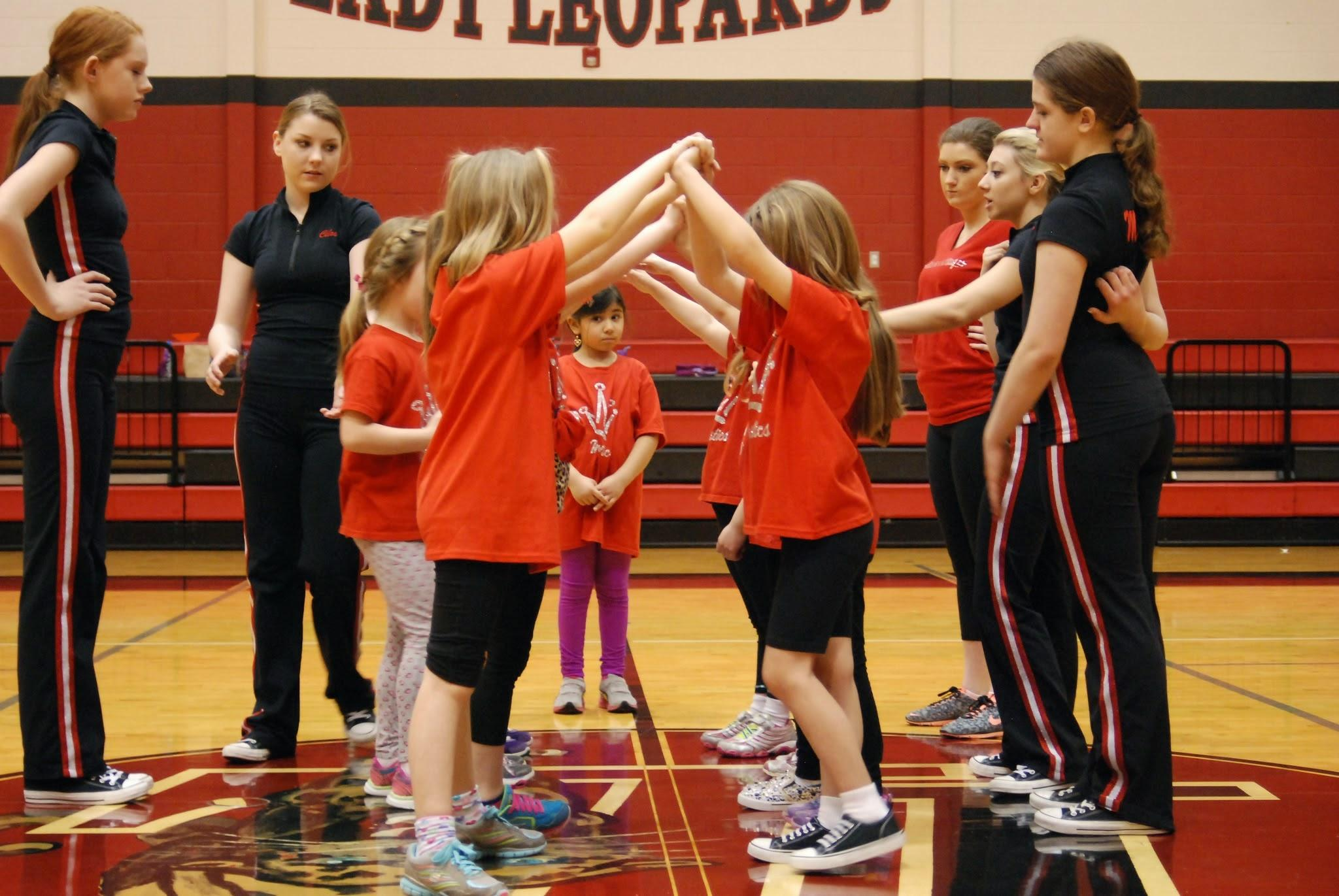 Elementary aged girls practice their tunnel dance move for their performance.