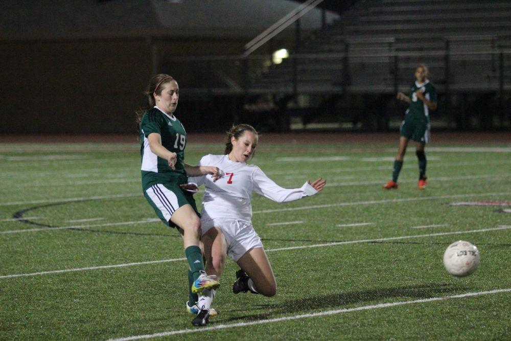Trying to regain possession of the ball, junior Jensyn Caton (7) tries sliding for the ball in the 2014-2015 season.