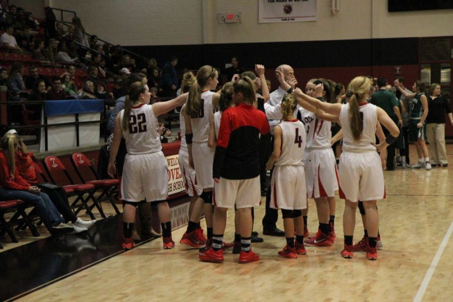 The girl's basketball team puts their hands in the middle to rally team spirit following a timeout.