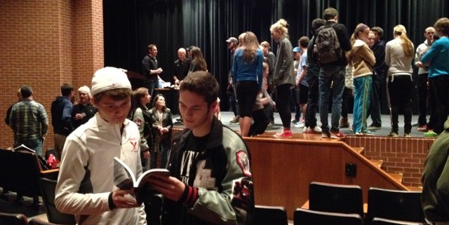 Juniors+and+cross+country+runners+Jacob+Myers+and+Brock+Bittner+flip+through+the+book+Running+the+Edge+after+getting+it+signed+by+the+authors+at+the+presentation+in+the+auditorium.+
