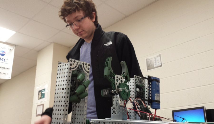 Maxwell Gifford works on programming his robot which will be able to pick up and grab objects, and move.