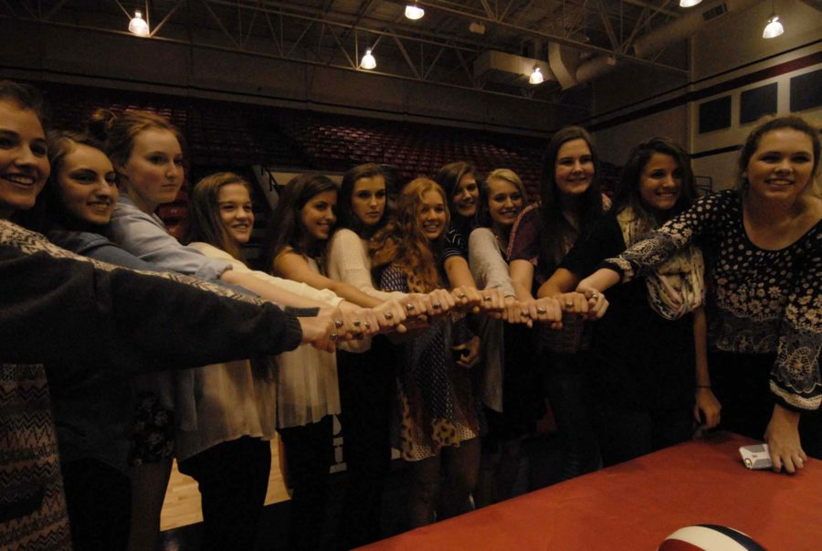 The volleyball team poses with their new State rings.