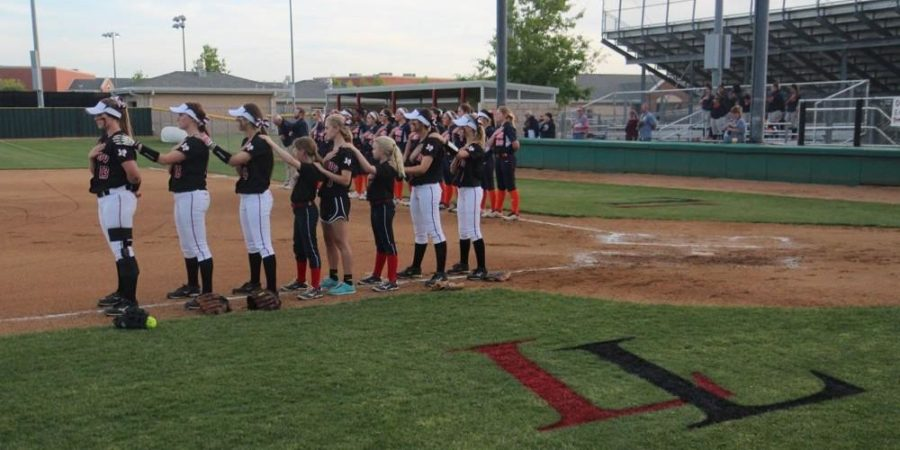The Leopards line up in the infield for the playing of the national anthem shortly before the game.