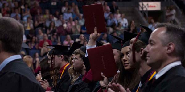 With the crowd applauding, some 2014 graduates raise their diplomas.