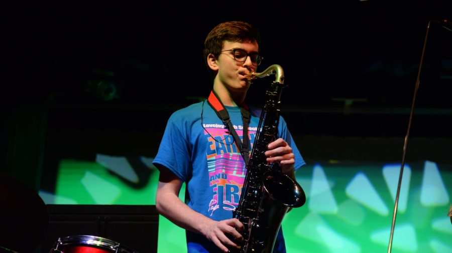 Junior singer, Jack Shore, shows off his musical abilities by accompanying the Spotlight group with his saxophone.