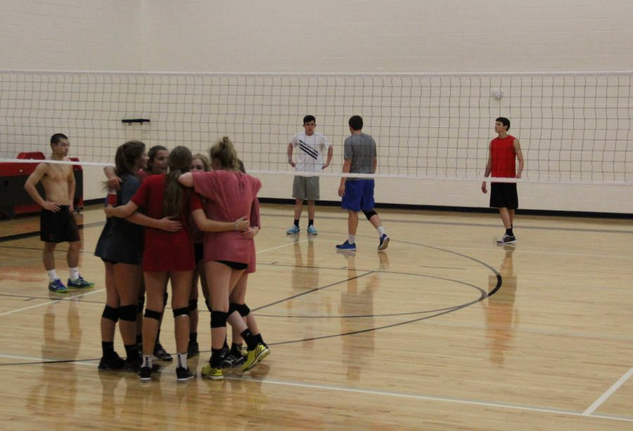 After winning the first set, the girls huddle after switches sides of the court to strategize.