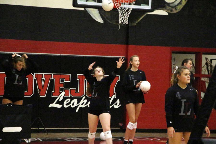 Senior Caroline Johnson tosses the ball to practice serving before the game.