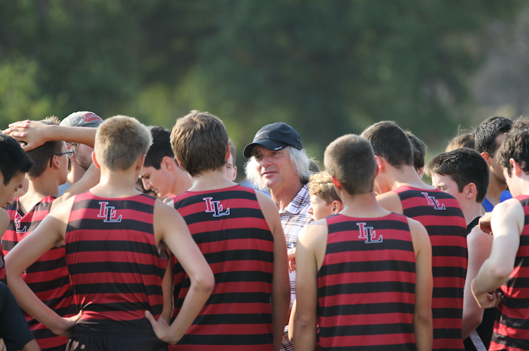 Greg+Christensen%2C+head+coach%2C+talks+to+the+JV+boys+in+their+iconic+stripped+uniforms+on+the+start+line+before+their+race.