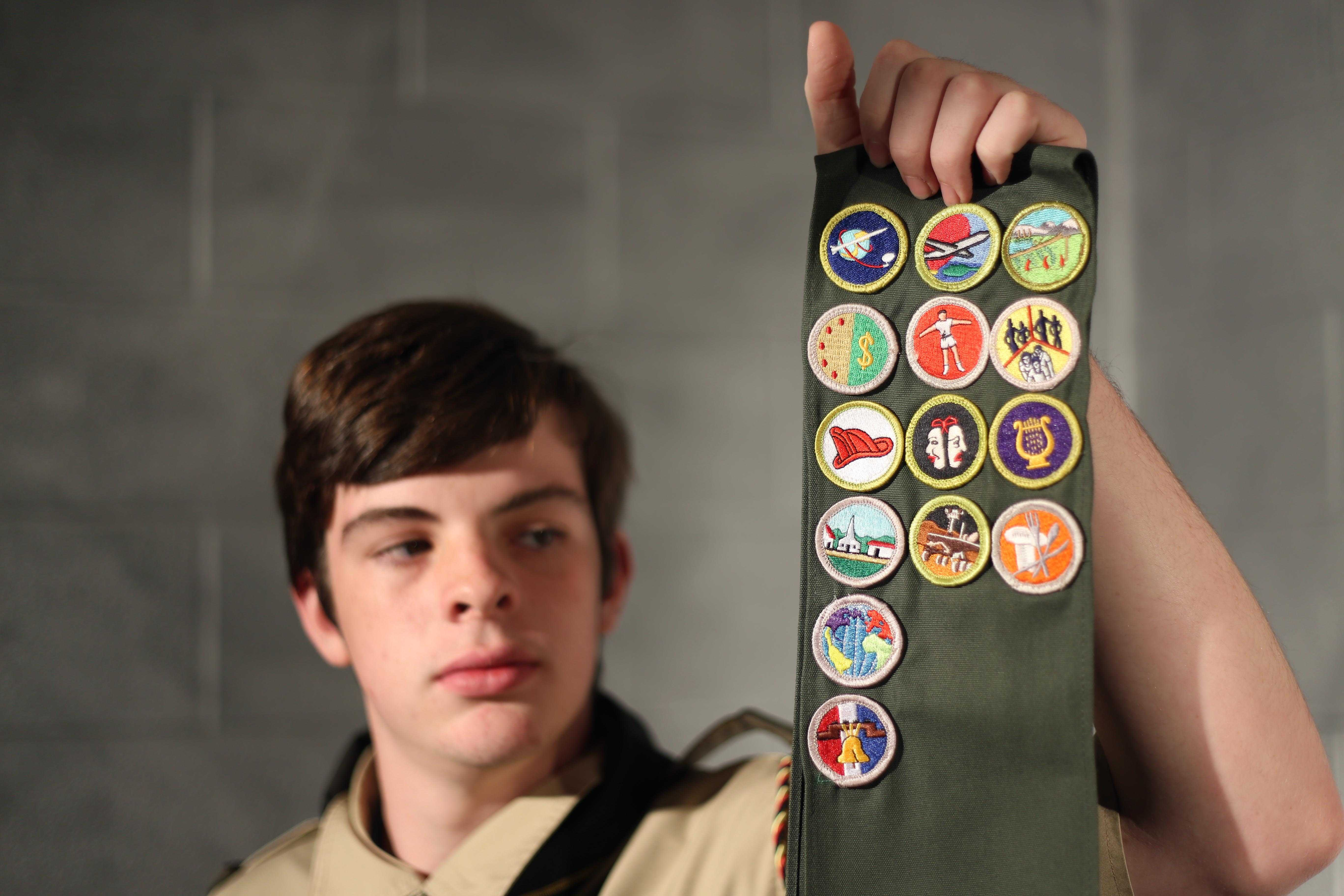 Landon Bruner holds up his Eagle Scout patches which reflect the hard work he does for the community.