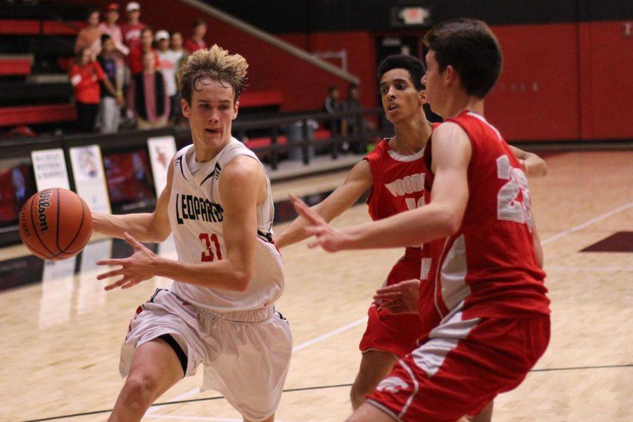 Varsity basketball player junior Braden Ledebur dribbles down the court in this year's season opener.