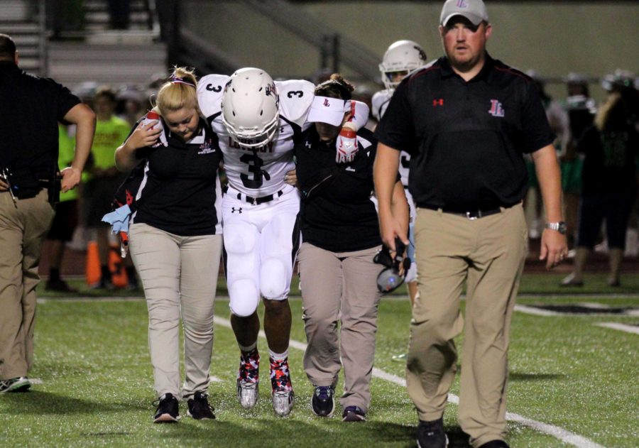 Athletic trainers Lauren Payne and Susan Smiley help injured player Blake Pfaff off the field.