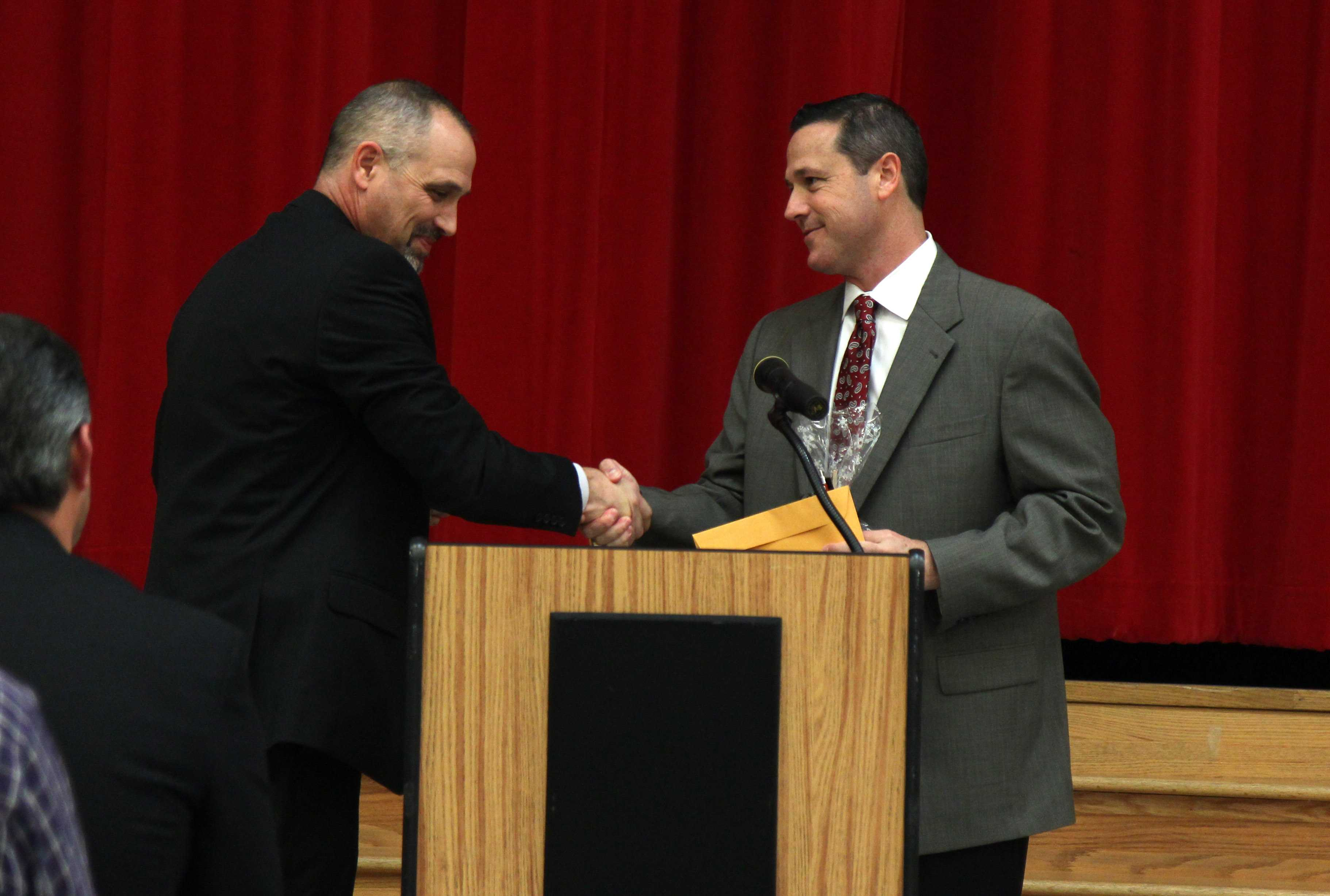 New head football coach Todd Ford receives his contract from principal Chris Mayfield after being confirmed by the school board on Wednesday night.