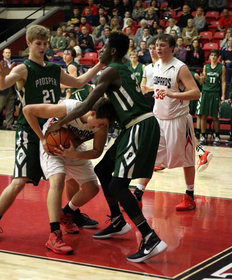 Surrounded by opposing team, Prosper, freshman Micheal Difiore tears ball away from opponent.