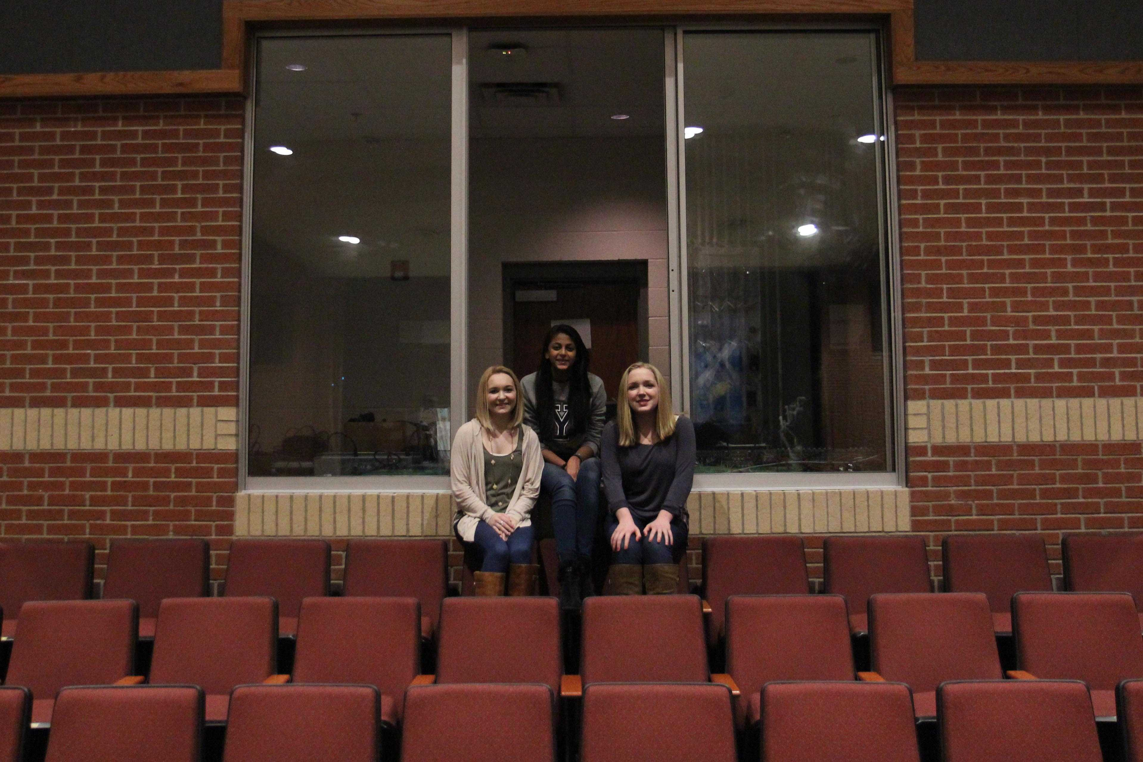 Three stage managers from recent shows, sophomore Mason Taylor Long, senior Sonali Mehta, and sophomore Lauren Latour, sit on the edge of the sound and light booth looking towards the stage.