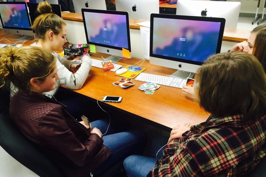 Students in Jennifer Holcombs fifth period photojournalism class play Uno during the Internet outage on Thursday. The students served as models for other photographers taking action photos while Photoshop was unavailable.
