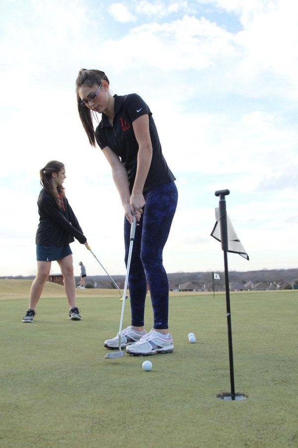 Senior Jazzy Veatch carefully puts the ball into the hole during the golf team's last tournament.