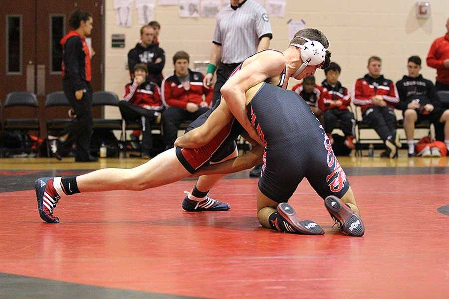 Junior Parker Rexford (left) grapples with his Coppell opponent during a meet at Sloan Creek on Jan. 22. Both boys and girls are in action at the district meet today.