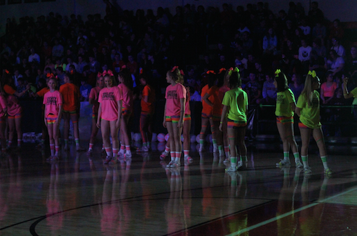 Wearing their specific grade level's T shirts, the cheer leaders put on a black light performance with multiple stunts.