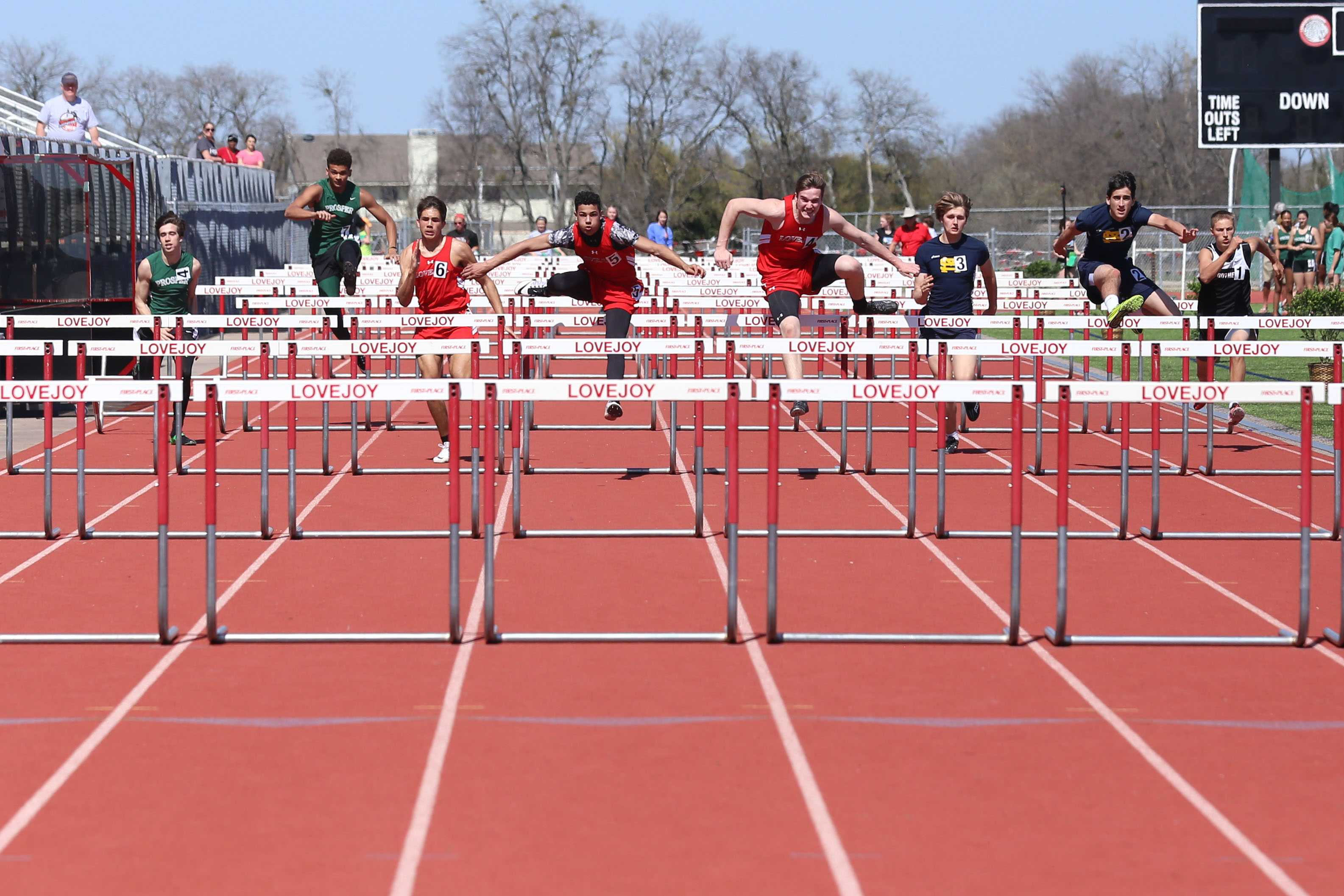 Neck and neck with Tyler Van-Wagoner (5), sophomore Reece Field (4) comes over the hurdle. Field placed first in the 100 meter hurdles with Van-Wagoner coming in just .02 seconds behind, placing second. Blake Pfaff, also pictured came in fourth.