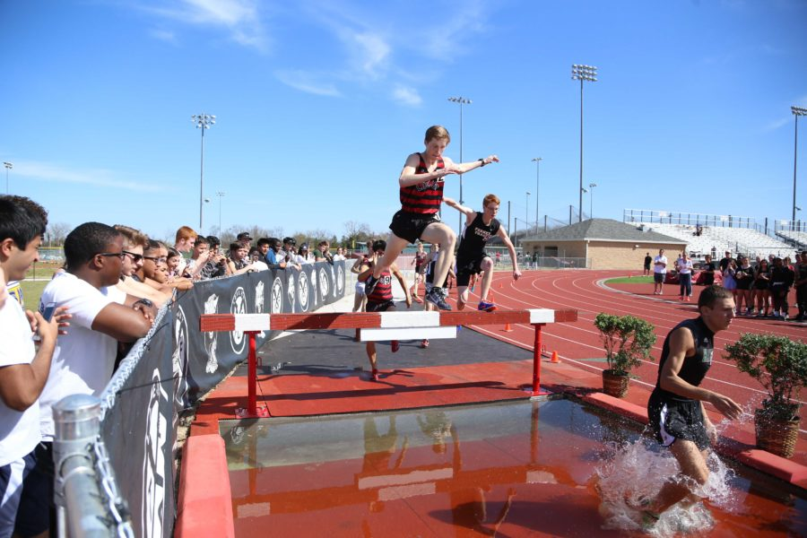 One of the more interesting races of the track meet, a Lovejoy runner comes over one of the steeplechase hurdles into the pool of water on the other side. He eventually placed first in the 2000 meter race, setting the state and national record.