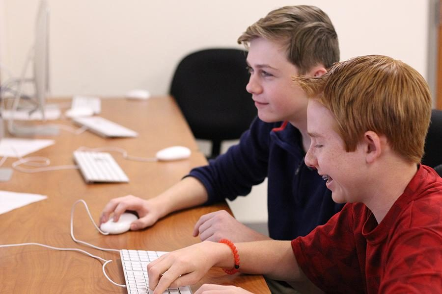 Two of the three team members, Pierce Richardson and Caiden Tays, work on developing their website during class.