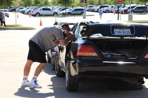Senior Clayton Bilke leans against a wrecked car in distress during the Shattered Dreams program. In the reenactment, Bilke's decision to drive while intoxicated resulted in the deaths of two students and the paralysis of a third.