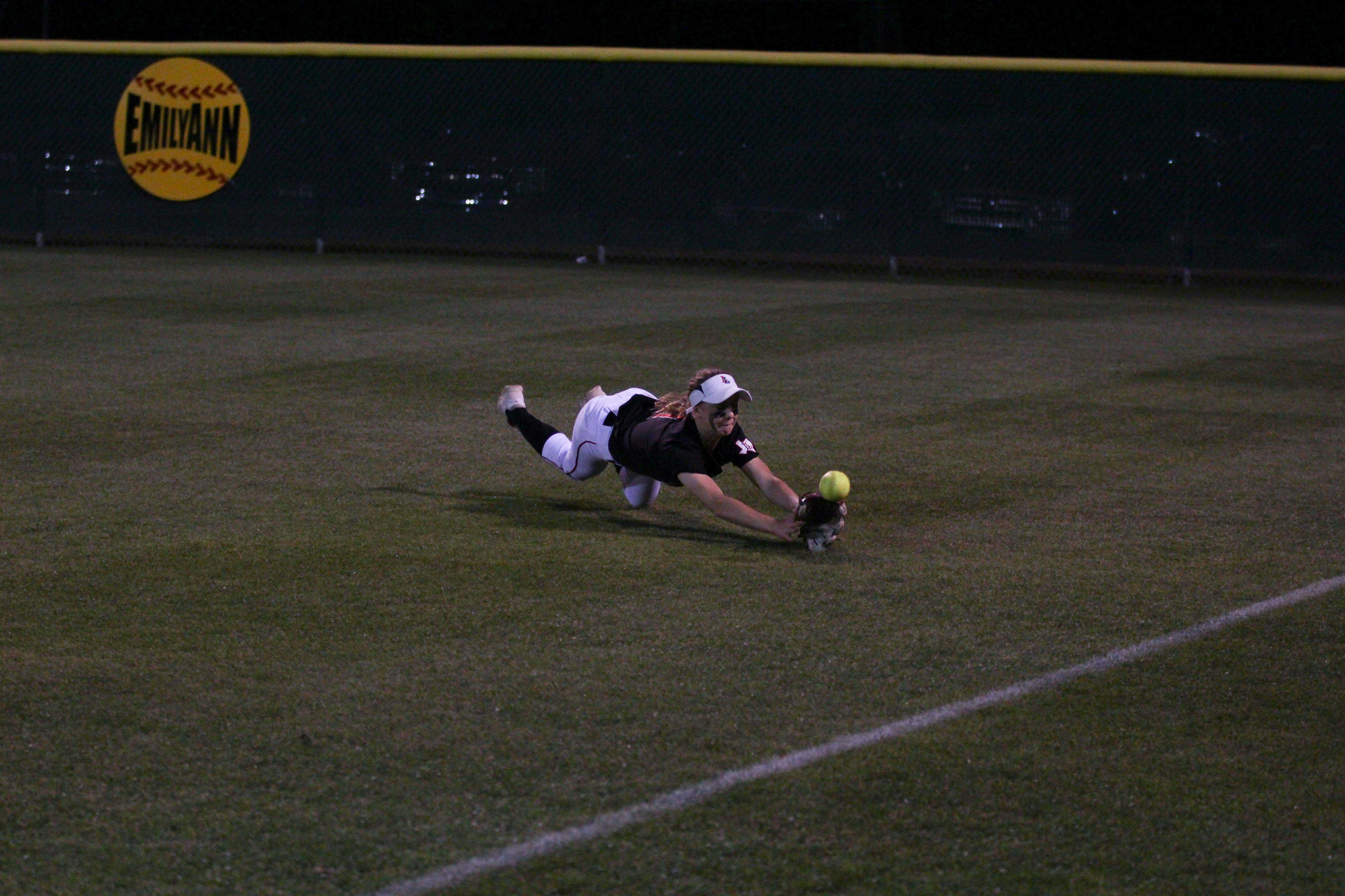 Sophomore Kim Lyne, playing right field, attempts to catch a fly ball in the outfield.